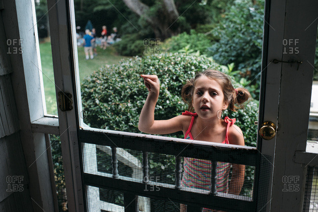 Little girl looking in through screen door and pointing
