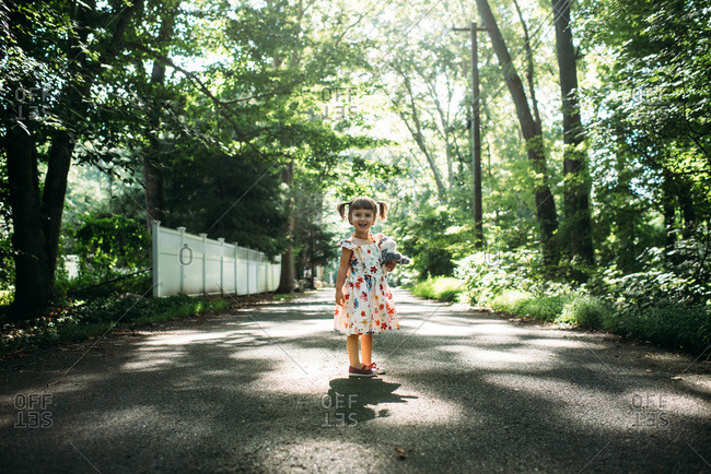 Little girl in flowered dress in walking down a tree covered street holding a stuffed cat