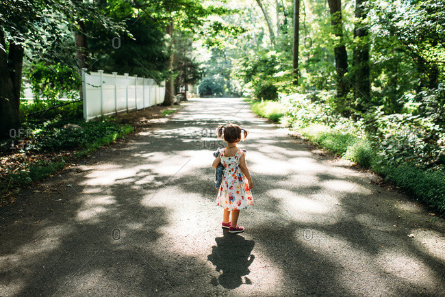 Little girl in flowered dress walking down a tree covered street holding a stuffed cat