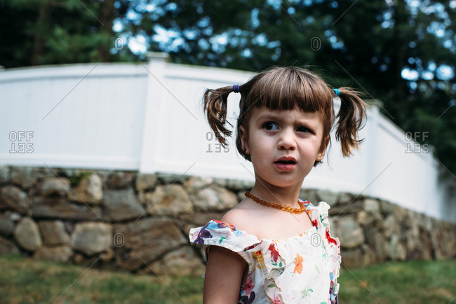 Little girl outside in front of a fence making funny faces