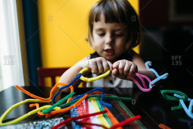 Little girl playing with colorful pipe cleaners