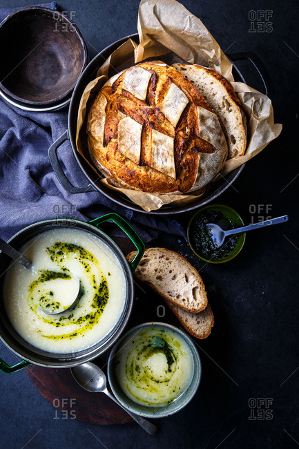 Potato soup with pesto being served with sourdough bread