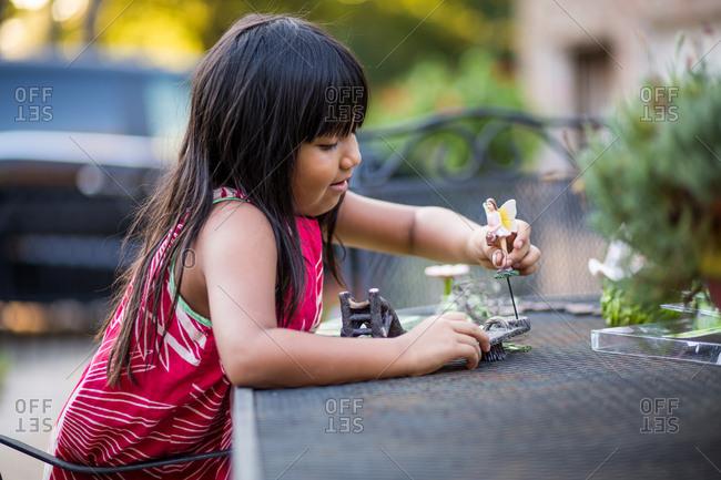 Girl arranging garden figurine and decor