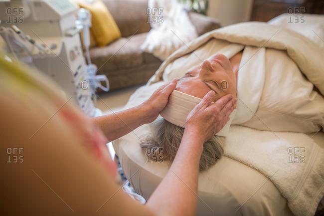 Woman wearing a headband receiving a face massage
