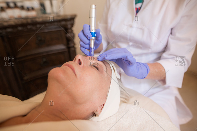Woman lying down with eyes closed receiving skincare treatment