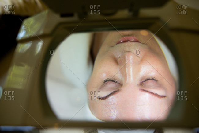 Woman's face viewed through magnifier lamp