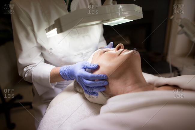 Woman lying under a lamp receiving a face massage