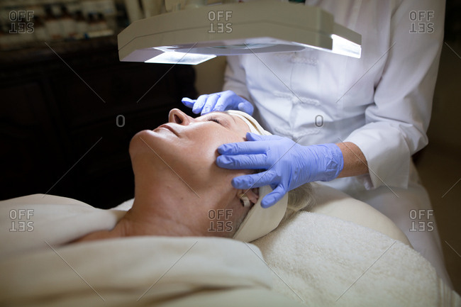 Woman lying under lamp receiving face massage from cosmetologist