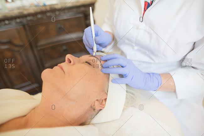 Woman receiving micro blading procedure