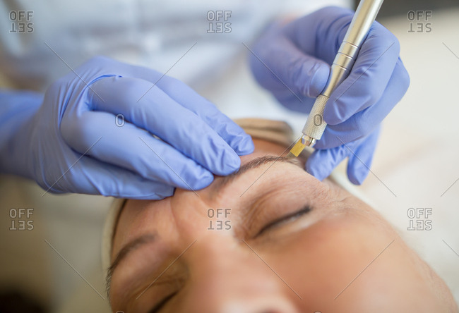 Close-up of woman receiving micro blading procedure on her eyebrows