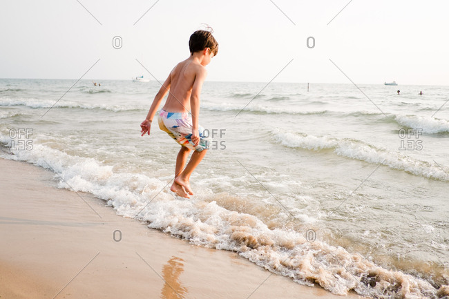 Boy jumping in the waves on the beach