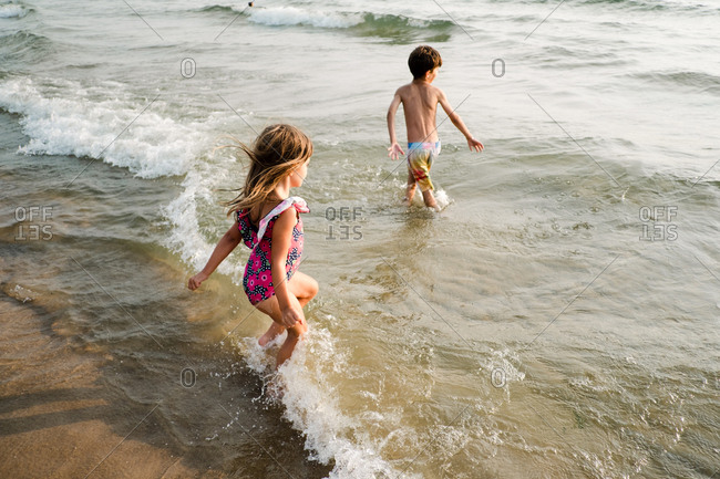 Children wading in the water together at the beach