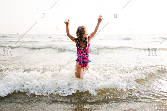 Girl with arms up standing in the ocean as waves splash around her