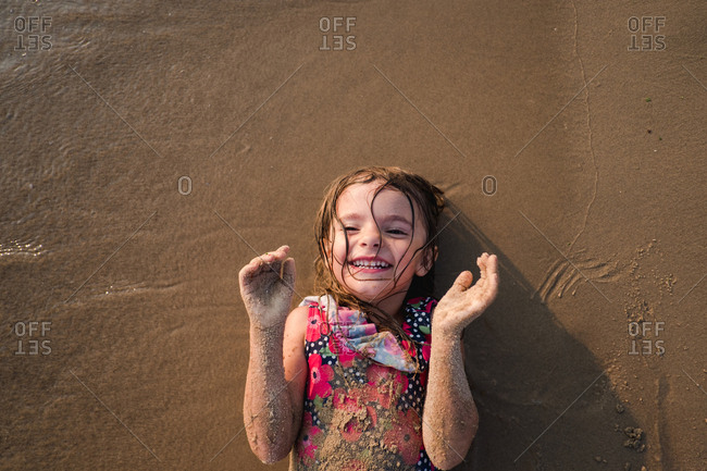 Smiling girl covered in wet sand lying on the beach
