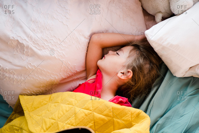 Girl sleeping in bed with pillows and blanket