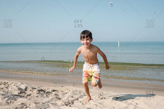 Smiling boy running from waves on the beach