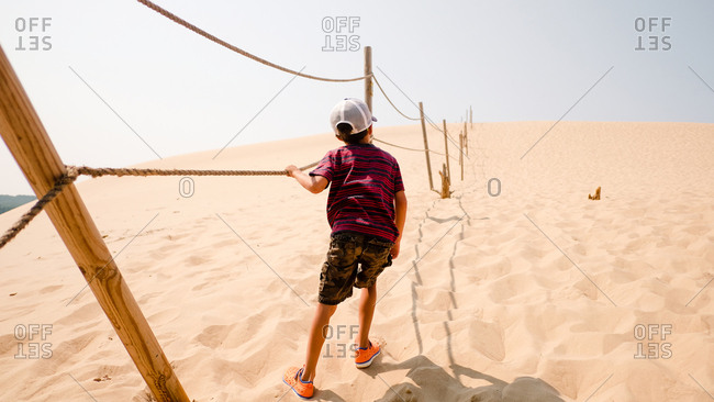 Child holding on rope to guide through sand dunes
