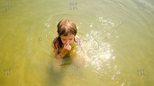 Girl holding her nose and taking a deep breath while swimming outdoors