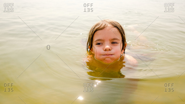 Portrait of a girl holding her breath while swimming with her head above water