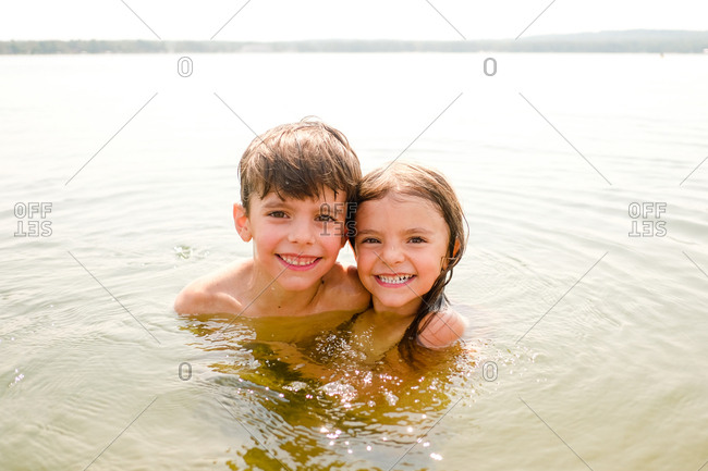 Portrait of brother and sister swimming together outdoors