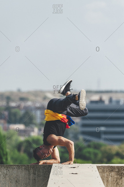 Young hispanic latin break dancer performing a dance pose over architectural structure with colombian flag in his hands