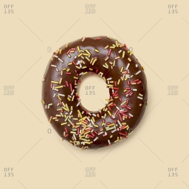 Chocolate doughnut with sugar strands, studio shot.