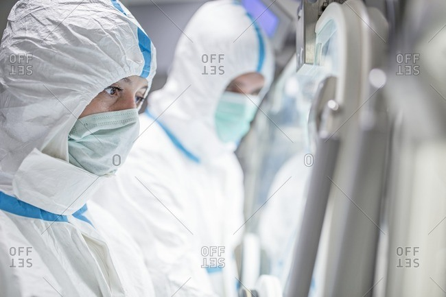 Technicians working in sealed, sterile isolator units in a laboratory that manufactures human tissues for implant. Such tissues include bone and skin grafts.