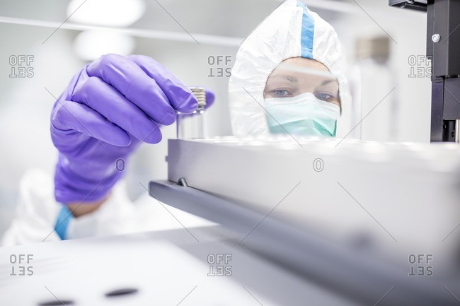 Technician checking stem cell cultures in a laboratory that manufactures human tissues for implants. Such implants include bone and skin grafts.