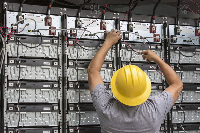 Engineer connecting energy storage batteries for backup power to an electric power plant.