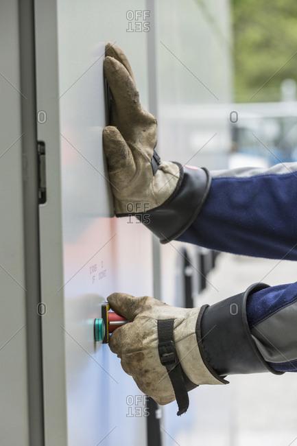 Close-up of an engineer closing steel enclosure door.