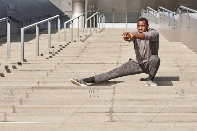 Young confident African American sportsman in activewear warming up on concrete steps  while having outdoor workout in downtown