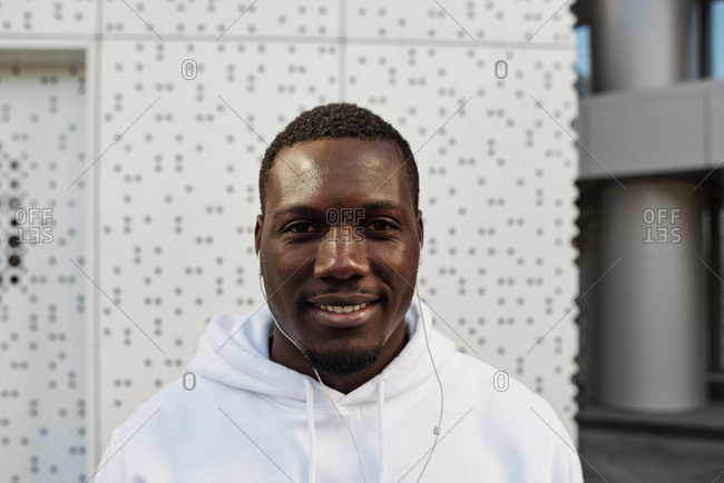 Waist-up portrait of young handsome Black man in white hoodie with earphones smiling at camera while standing against modern business center