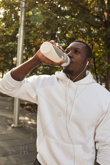 Young thirsty athletic Black man wearing white hoodie drinking water from sport bottle after long distance running outdoors