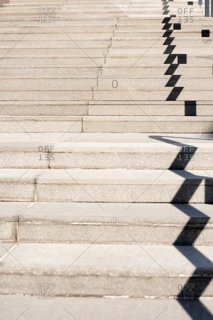 Stairs geometry. Conceptual shot of concrete steps with railing shadow outdoors