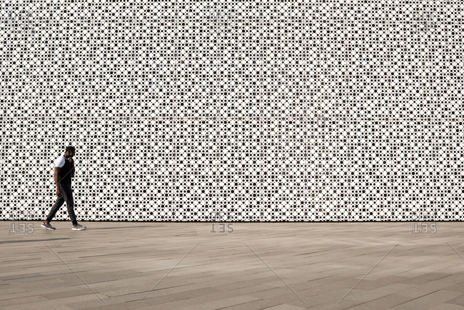 Unrecognizable African American man in sportswear walking along modern business center with white perforated facade, copy space