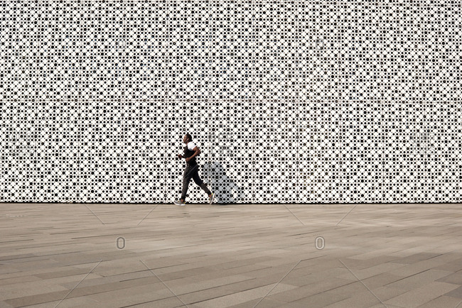 Workout in urban background. Black sportsman in activewear running along contemporary building with white perforated facade, copy space