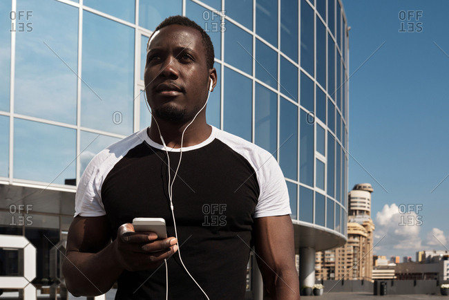 Low angle view of handsome African man standing against modern commercial building with smartphone, listening to music through earphones and looking into the distance