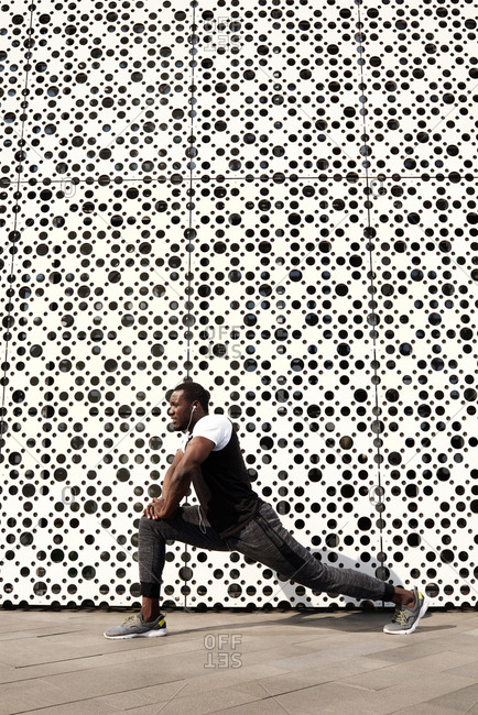 Young African American sportsman listening to music and stretching his legs outdoors against modern art center with white perforated facade