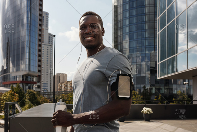 Waist-up portrait of handsome athletic Black man with earphones and smartphone in armband standing in downtown and smiling at camera cheerfully