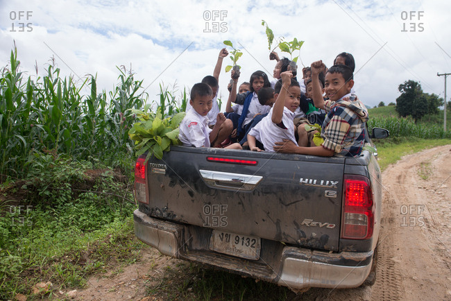 August 27, 2018: Asian Youth at the Back of Pickup Truck Rising Up Their Hands together, Ready for Planting Teak to Renew the Forest. Chiang Mai, Thailand.