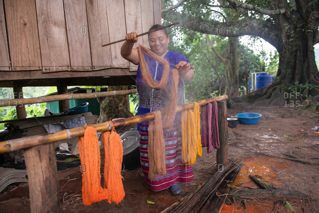 August 18, 2018: Asian Karen Hilltribe Woman Drying Dyed Fabric. Chiang Mai, Thailand.