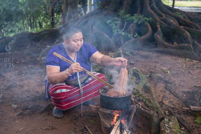 August 18, 2018: Asian Karen Hill Tribe Woman Dyeing Fabric. Chiang Mai,  Thailand.