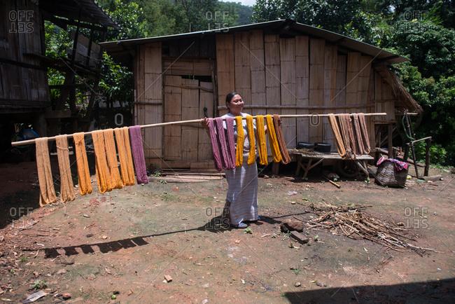 August 19, 2018: Asian Karen Hilltribe Woman Drying Dyed Fabric. Chiang Mai, Thailand.