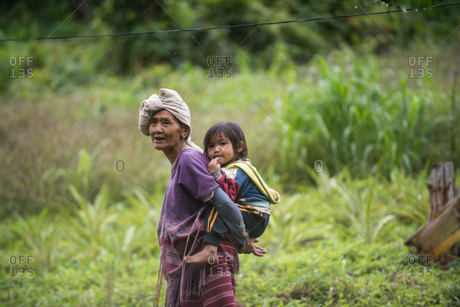 August 17, 2018: Portrait of Asian Karen Woman Carrying Her Grandchild on He Back, Chiang Mai, Thailand