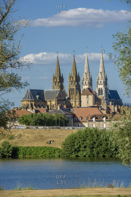 December 11, 2014: France, Auvergne-Rhones-Alpes, Allier, Moulins, Former capital of the Dukes of Burgundy seen from the left bank of the Allier river with both the steeples of Notre-Dame cathedral and Saint-Pierre church