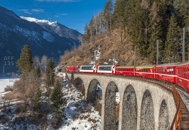 February 28, 2014: Switzerland, Albula Valley, viaduct and a Bernina Express train