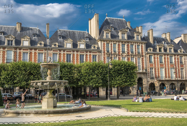 August 4, 2015: France, Paris 3th and 4th district, buildings and fountain in the public garden on place des Vosges