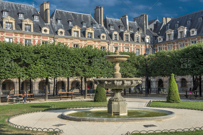 August 4, 2015: France, Paris 3th 4th district, buildings and fountain in the public garden on place des Vosges