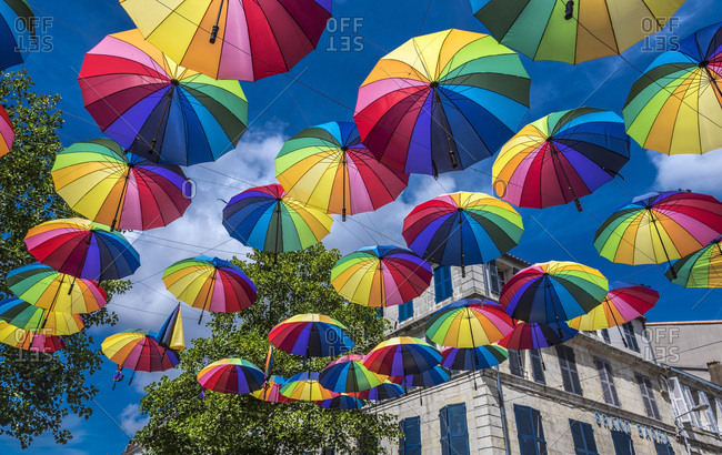 August 5, 2016: France, Charente-Maritime, Rochefort, street decoration with colorful umbrellas against a blue sky