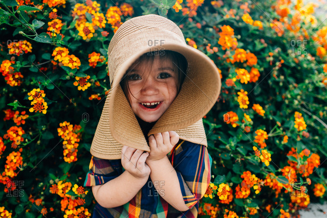 Toddler girl pulling on her big hat by orange flowers